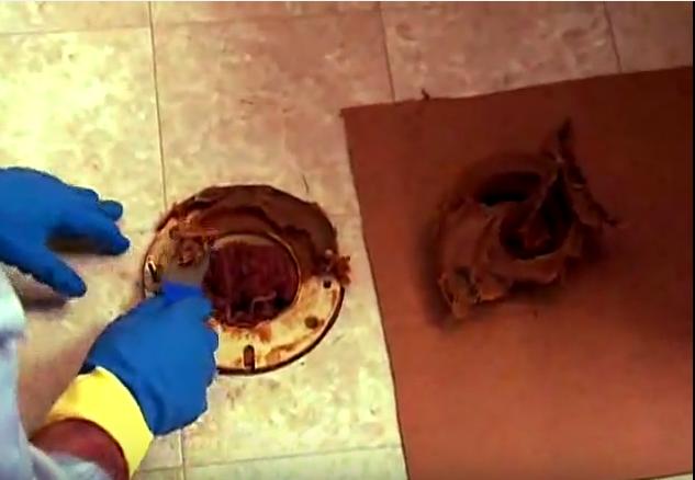 7. Dùng dao trát ma tít để cạo lớp keo dán của bồn cầu cũ